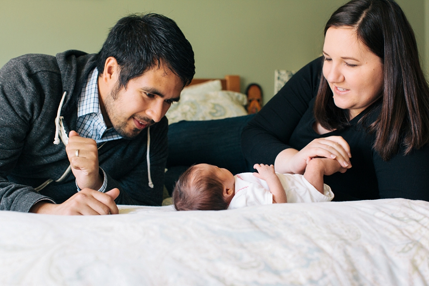 parents with newborn on bed, lacey monroe photography, lifestyle newborn photos