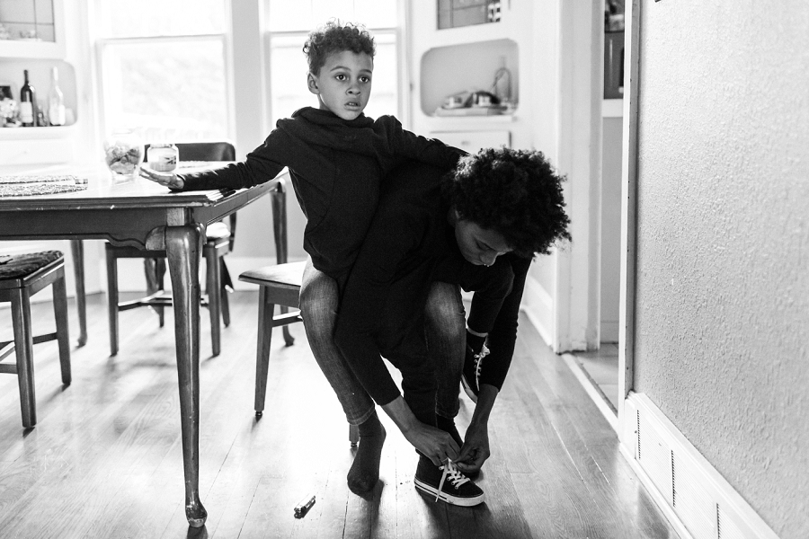 documentary family photographer, lacey monroe photography, mom ties shoes of boy