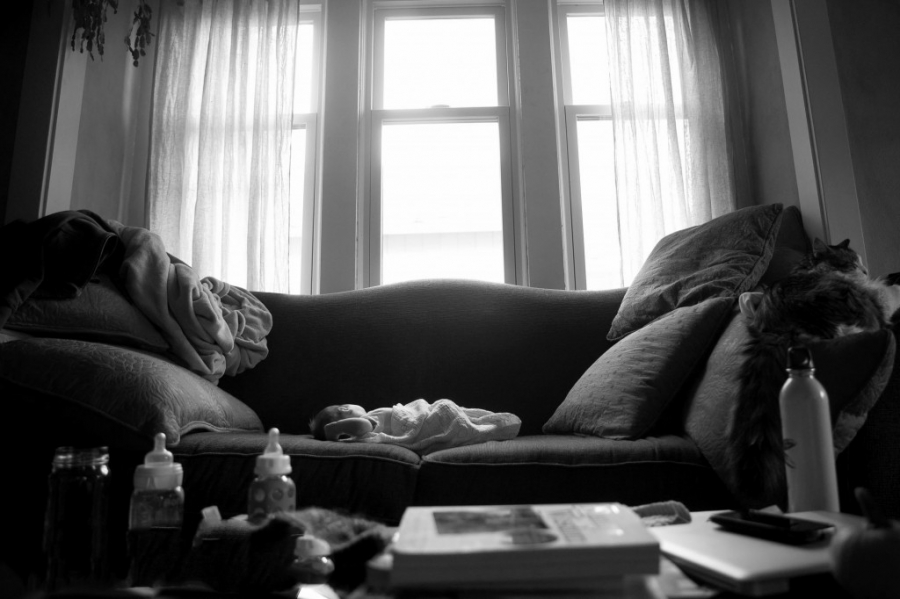 newborn baby sleeping swaddled in a muslin blanket on the couch, clutter on the table and all captured in this image