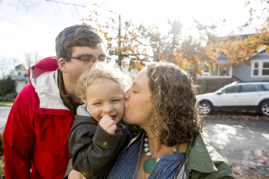 Photograph of 2-year-old toddler being hugged by his mom and dad with a really authentic smile on his face