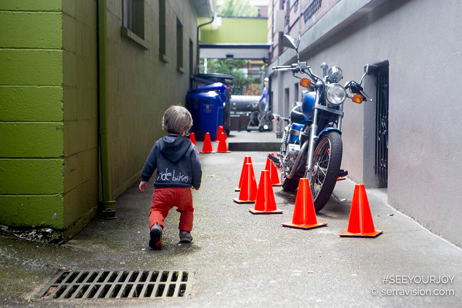 urban toddler adventures - toddler in bright orange pants heading down an alley with a motorcycle and traffic cones. this lifestyle children