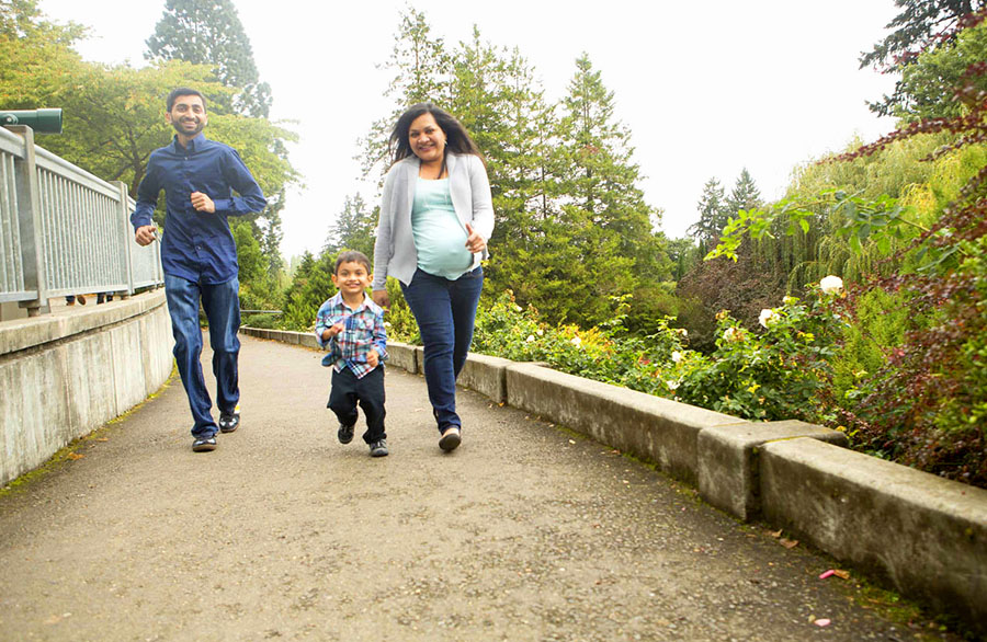 Pregnant mom, husband, and son race each other down the sidewalk