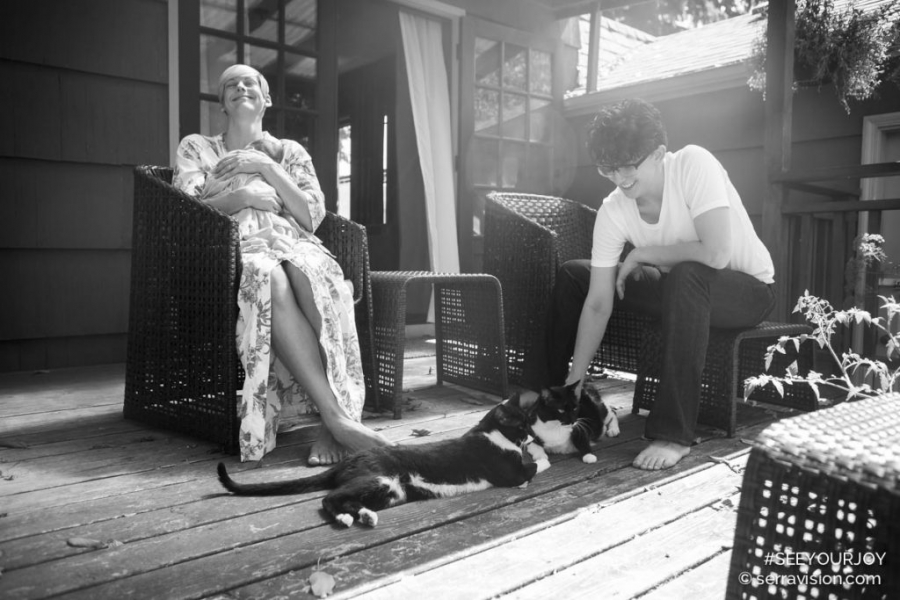 Lesbian couple hanging out and laughing outside their home with their newborn baby and two black and white cats.