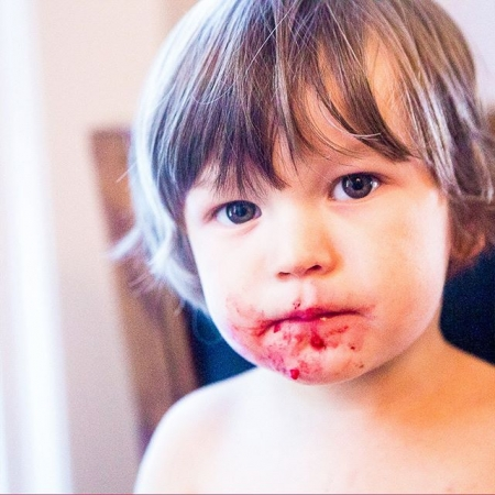 Close-up photo of a toddler with berry juice all over his face
