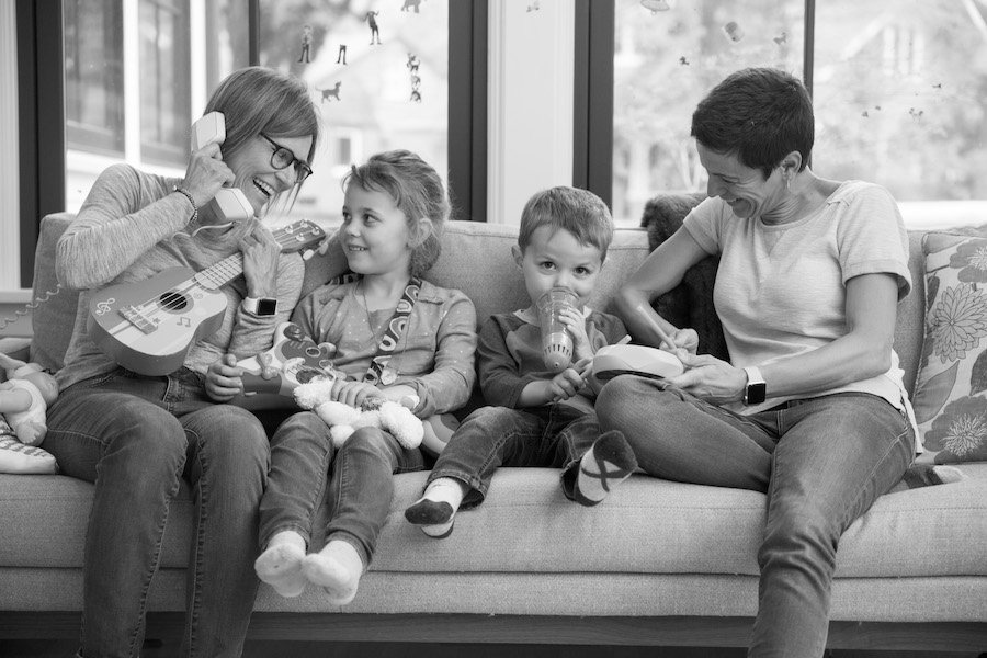 two moms with their preschool son and daughter sitting on the couch with musical instruments
